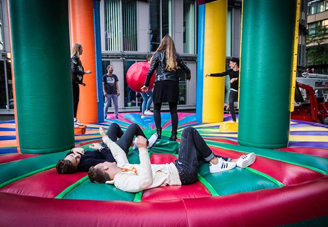 ASTA Studierende auf einer Hüpfburg. Zwei liegen auf dem Boden.