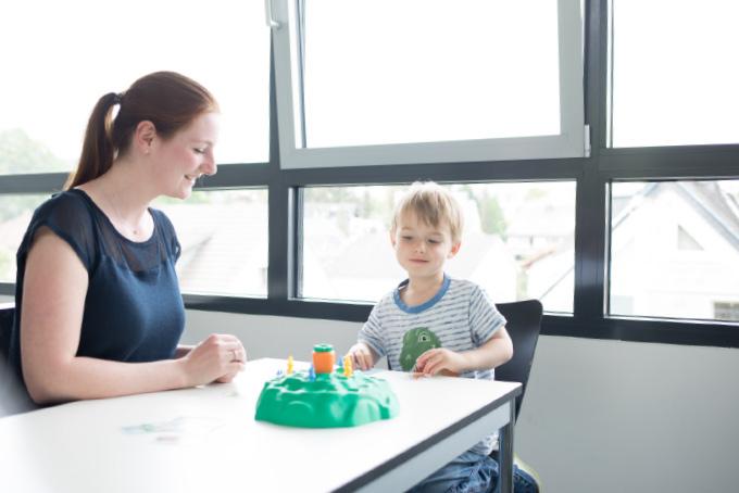 Junge Frau sitzt mit kleinem Jungen am Tisch. Vor ihnen steht eine grüne Burg mit einem orangenem Turm.