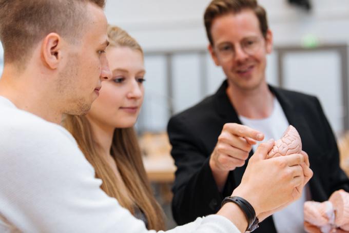Dozent zeigt Studenten ein Gehirn im stehen.