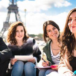 Studierende sitzen vor dem Eifelturm.