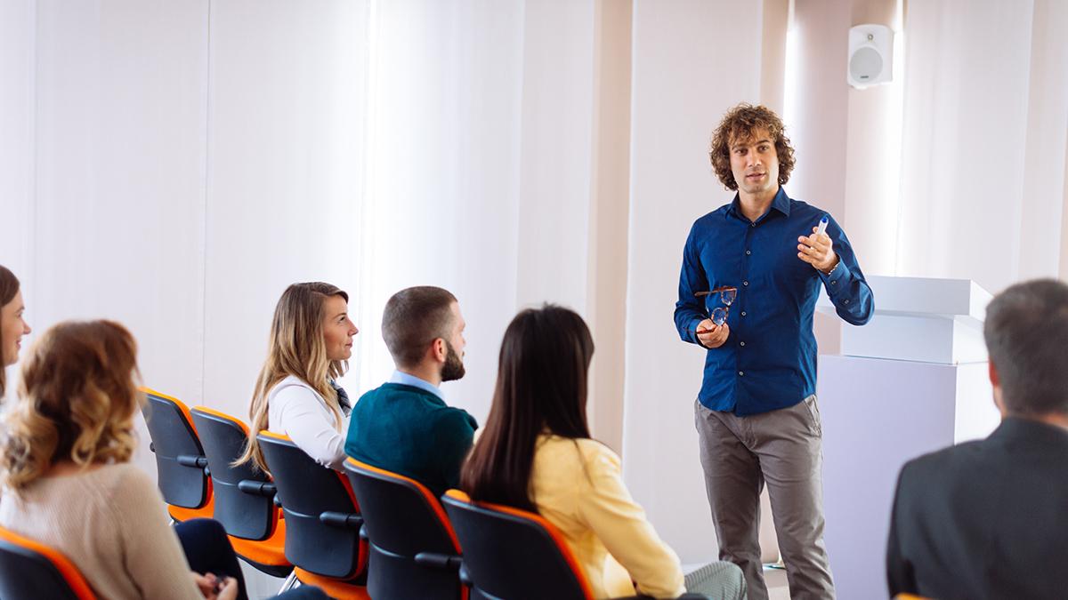 Dozent mit Locken und Brille spricht zu seinen Studenten.